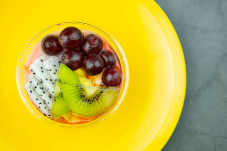 Healthy breakfast in plastic bowl with fresh fruits, Kiwi, grape and dragon fruit slice put on yellow dish Archivio Fotografico