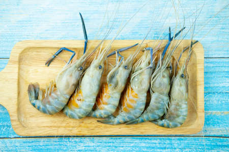 Fresh raw shrimp with a lot of eggs arrange on wood tray ready for cooking