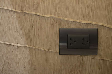 Black electrical outlet on wall in home at Thailand