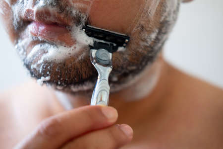 Young man with foam soap on his cheeks is standing and removing mustache by shaving from his face.