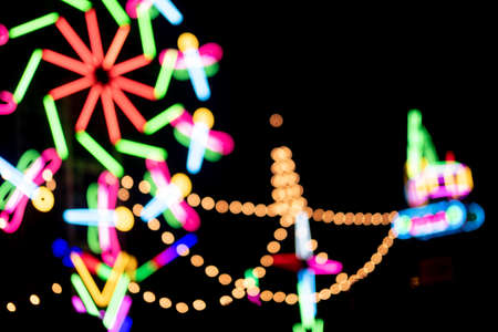 Blur colors light beam of fluorescent light colorful in festival temple fair night background, lighting beam in carnival colorful light shine show of thai temple fair festival color bokeh