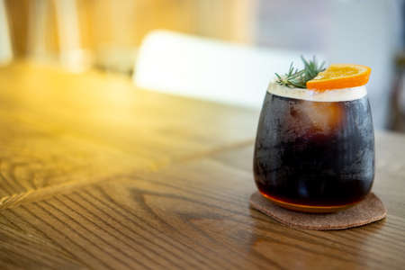 Glass of espresso shot mixed with orange juice on wood table. Refreshing summer drink concept