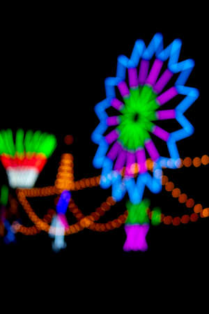 Blurred and defocus of colorful rotating lantern light turbine or color neon with black background at Thailand temple festival fair night party. Reklamní fotografie