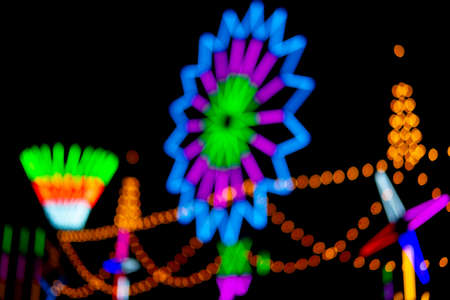 Blurred and defocus of colorful rotating lantern light turbine or color neon with black background at Thailand temple festival fair night party.