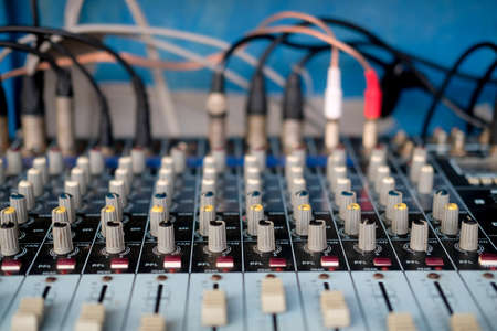 Audio mixing console with faders and adjusting knob