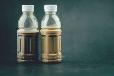 Tasty mocha coffee and cocoa milk in plastic bottle on black background