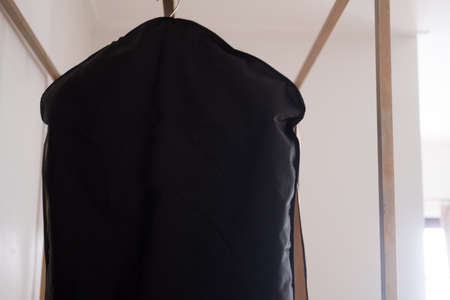 Black suit cover hanging on rack of clean clothes hanging. Close up