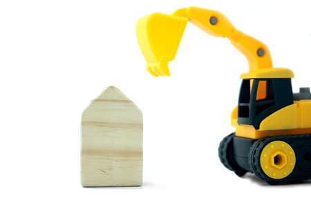 Wood home with yellow toy loader ready to move out on a white background