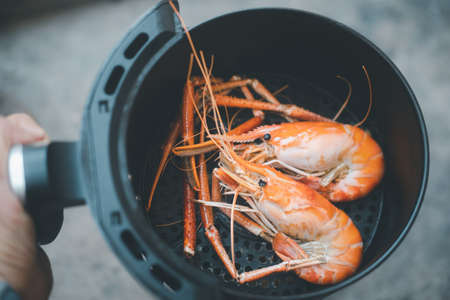 River shrimp cooked in black air fryer. Easy cooking in house concept Standard-Bild