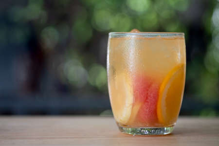 Refreshing summer homemade cocktail with lemon, lime, orange and grapefruit on wood table