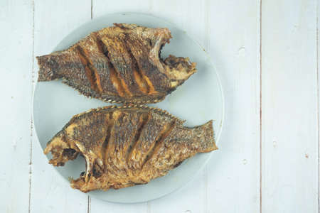 Thai food deep fried Tilapia fish on plate on wooden background.