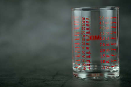 Glass of measuring cup with markings on a black background. Measuring liquids Stok Fotoğraf