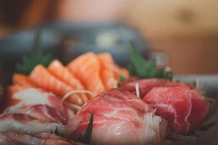 Fresh raw salmon fish sashimi is sliced in Japanese cuisine. Assorted fresh sashimi and Japanese food concept. Selective focus