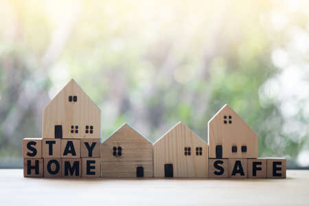 """""""STAY HOME STAY SAFE"""" text on wooden blocks and miniature home wooden. Stay home concept of self-isolation during the Covid-19 coronavirus outbreak and copy space Foto de archivo"""