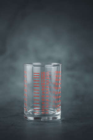 Glass of measuring cup with markings on a black background
