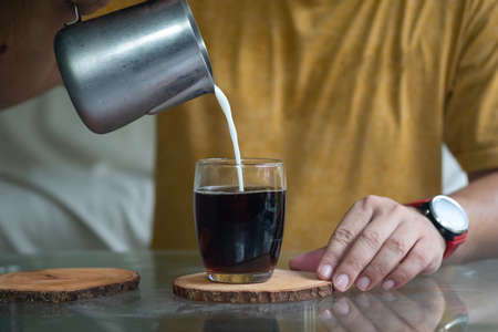 Milk pouring from a small pitcher by a man's hand from above into glass with black coffee.