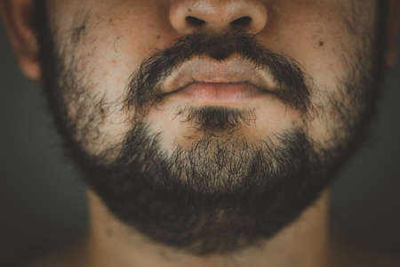 Close up half face of a Asian man with a beard and thick mustache