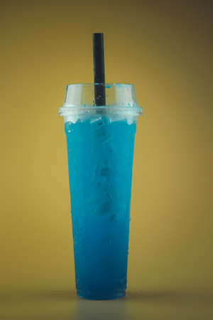 Iced blue lime soda in tall plastic glass with black straw