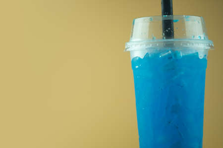 Iced blue lime soda in tall plastic glass with black straw. Use photo for beverage menu