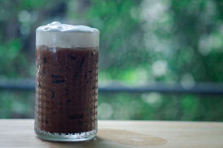 Iced coffee with milk cream in a tall glass on wood table