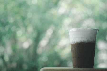 Iced Mocha coffee in takeaway glass and milk foam with nature background. Show Layer milk foam and coffee