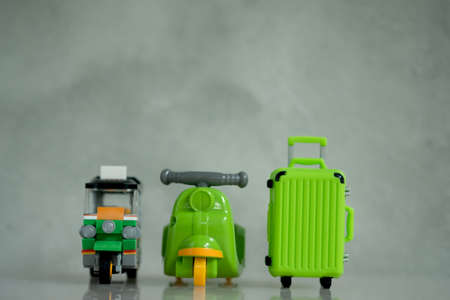Miniature green tuk-tuk, green motorcycle and green suitcase for travel in Thailand. Concept of new normal travel Stock Photo