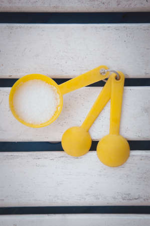 Yellow measuring spoons with sugar on white wood table