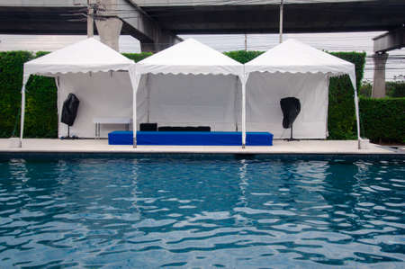 Stage and loudspeaker with tent near swimming pool to prepare outdoor event. Concept of party outdoor