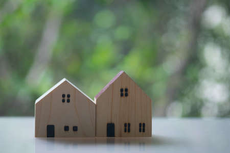 Two of lovely small model house with nature green bokeh sunlight abstract background. New property investment concept.