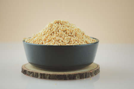 Ground peanut powder in black bowl ready to cook