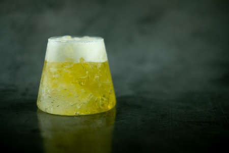 Cold beer with foam in a small glass and a black background with blank space for text