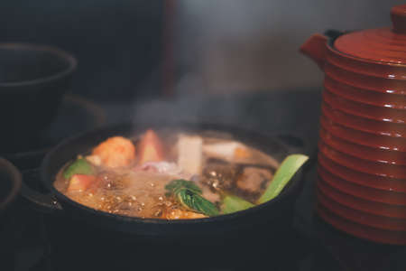 Japanese Sukiyaki pork, beef and mix vegetable boiled in black soup in traditional cast iron pot. Selective focus
