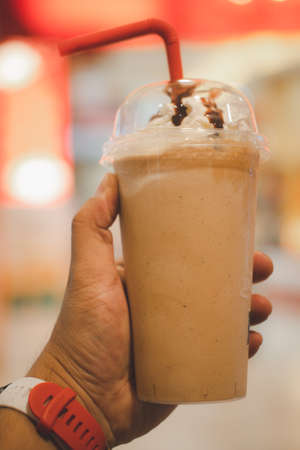 Cold cofffee blended with whipped cream on top and red tube. Close up on hand
