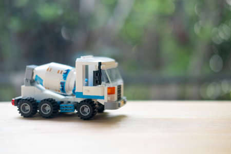 Concrete mixer truck plastic toy on wood table. Close up.