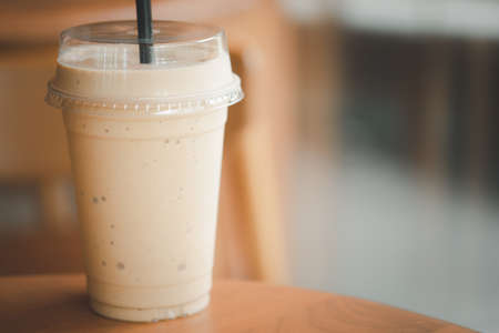 A plastic cup of ice smoothie coffee on wood table