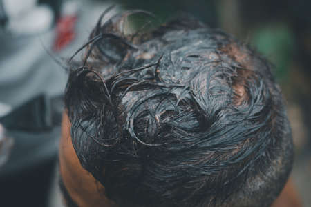 Old man dyes his hair in home. Coloring of men hair. 스톡 콘텐츠