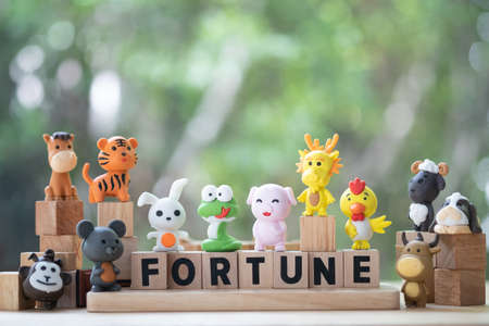 Cute animal in the Chinese zodiac with wood block text with fortune. Concept of fortune in life