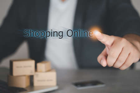 Businessman pressing button with contact on virtual screens word of Shopping Online. Concept of E-commerce 写真素材