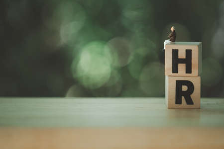 Miniature people sitting on wood blocks,with letters H and R, spelling is Human Resource against on a nature background. Concept of Human resource management