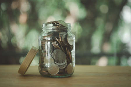 Transparent glass savings jar filled with Thai coins on wooden table with nature background. Saving money concept