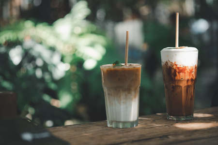 Glass of iced latte coffee and iced mocha placed on wood table with garden background at outdoor cafe