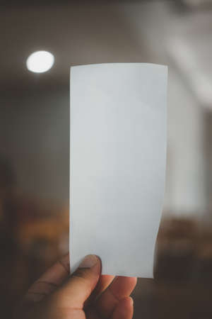 Person's hand holding empty paper bill. Selective focus