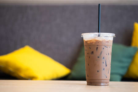 Iced mocha coffee in plastic cup showing the texture and refreshing look of the drink with sofa background