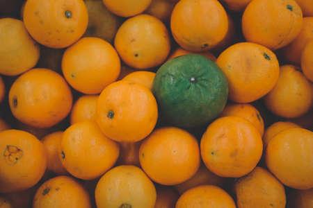 Stack of orange fruit with one green orange placed on top stock orange fruit at market