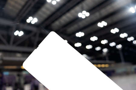 Close up of holding paper airplane ticket, blurred light background at airport.