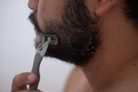 The man is shaving. Personal hygiene, body hygiene
