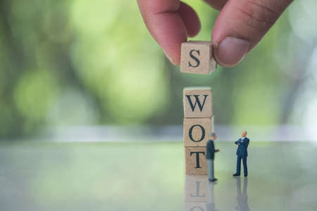 Hand putting wooden cube of S on W, O, T beside miniature people businessman meeting. SWOT Abbreviation Of Strength, Weakness, Opportunities, Threats 免版税图像
