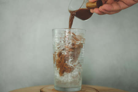 Pouring coffee into glass on ice. Preparing iced Mocha