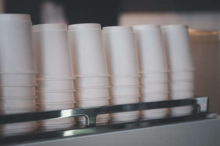 A lot of recycle white paper cups Upside down on coffee machine 免版税图像