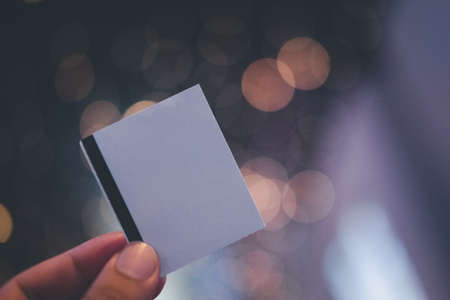 Male hand holding blank sheets of paper (tickets, flyers, invitations, coupons) on bokeh light background 免版税图像